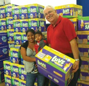 Baby Basics' volunteer, Wayne Antworth, distributes diapers – and kindness – to one of the many families who participate in this important program.